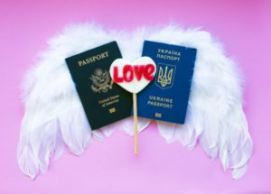 two passports laying on top of white feather angel wings