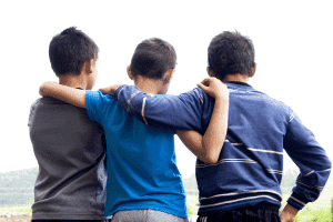 three young boys with their arms wrapped around each other